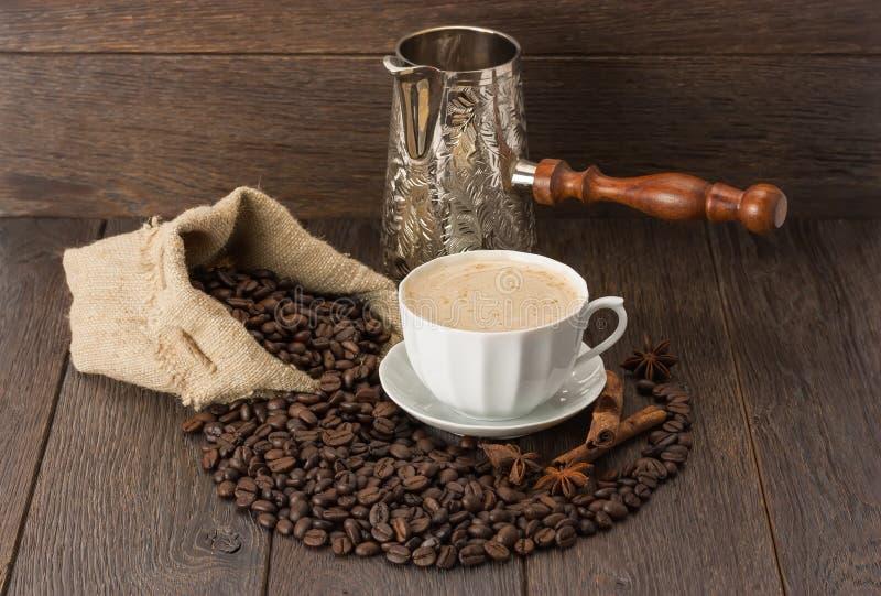Een Kop koffie en koffiebonen op houten lijst royalty-vrije stock afbeelding