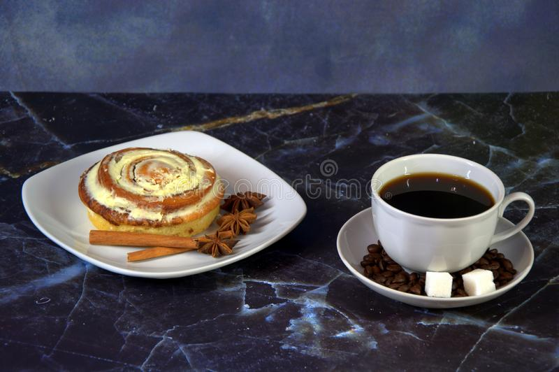 Een kop koffie op een schotel met suikerblokjes en koffiebonen, naast een bord met een kop in glazen versierd met kaneel en stock afbeeldingen