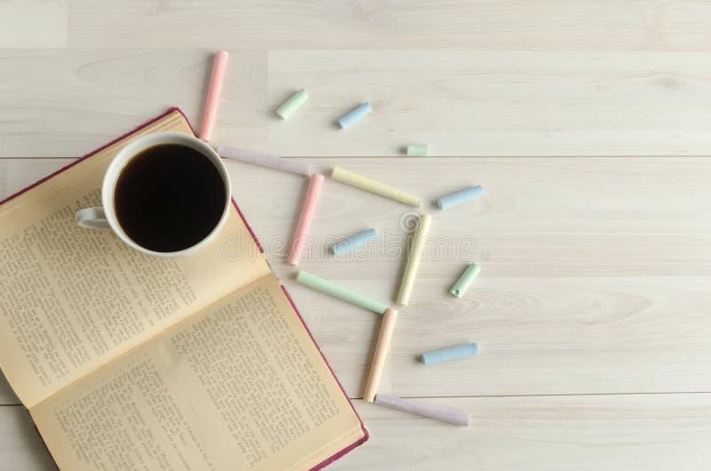 Een kop koffie, een open boek en multicolored krijt op een witte houten achtergrond De dag van het wereldboek, copyspace stock afbeelding