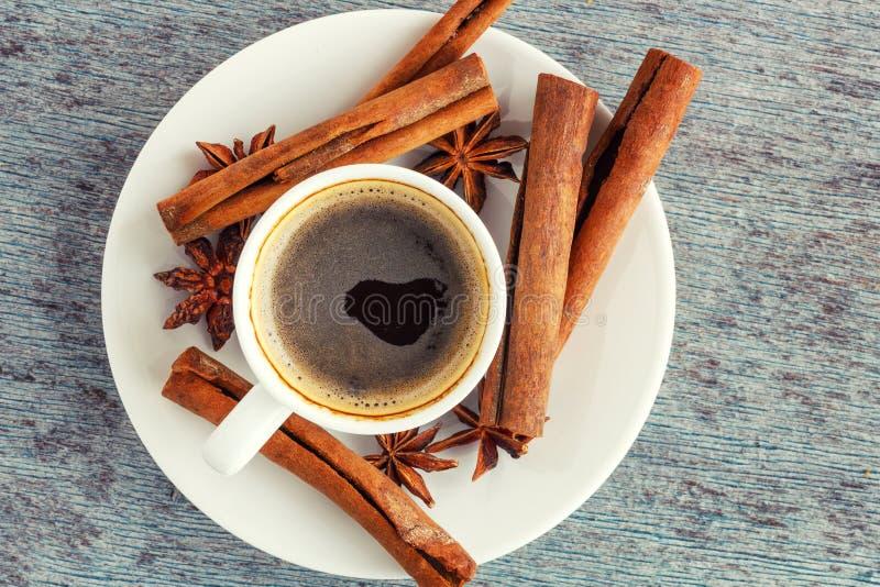 Een kop koffie, pijpjes kaneel en anijsplantsterren op houten bac royalty-vrije stock afbeeldingen