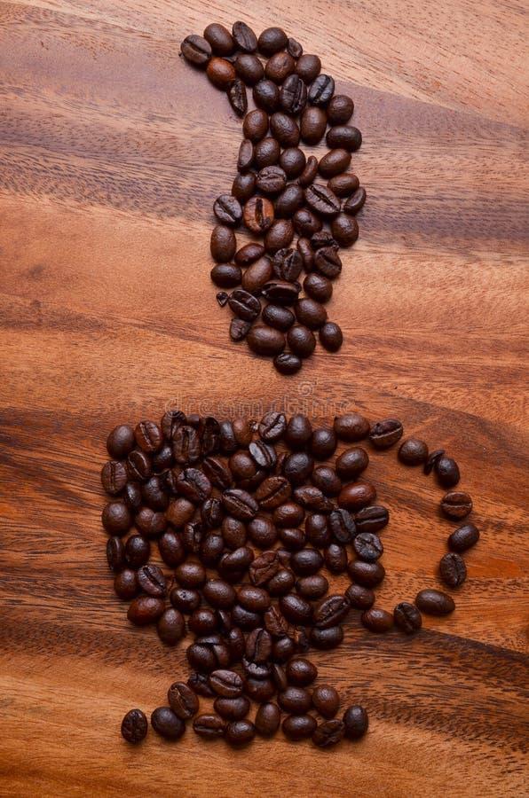 Een kop koffiebonen op houten achtergrond stock foto's