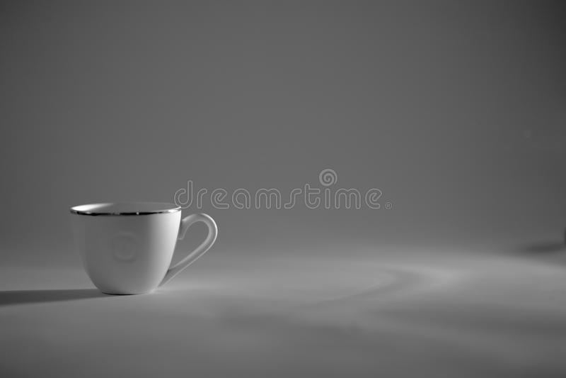 Een Kop koffiekosten in een zwart-wit lichtstraal, royalty-vrije stock foto's