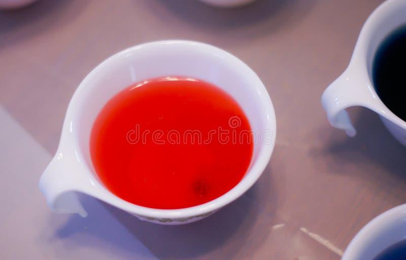 Een kop met rode kleurstof voor het verfraaien van eieren voor Pasen stock afbeelding