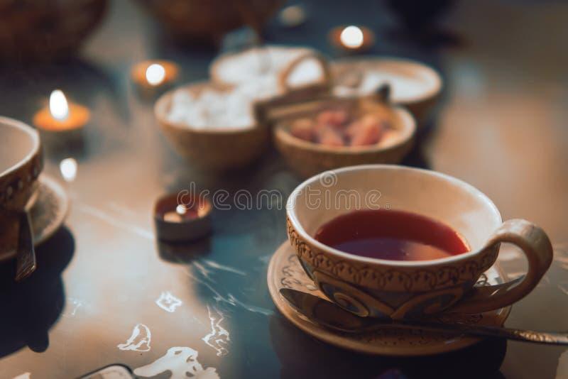 Een kop rode thee en suikerkubussen met verschillende smaken, met de hand gemaakt, op de glaslijst, oostelijke theeceremonie donk stock fotografie