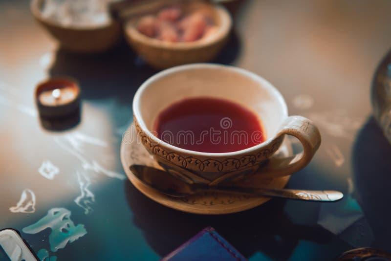 Een kop rode thee en suikerkubussen met verschillende smaken, met de hand gemaakt, op de glaslijst, oostelijke theeceremonie donk stock foto