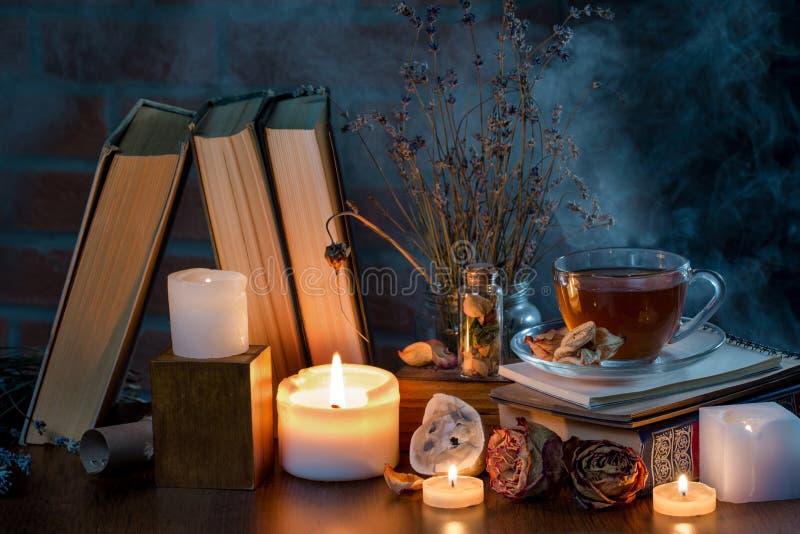 Een kop thee, boeken, kaarsen, rook Geheimzinnig donker stilleven Droge bloemen Feeatmosfeer royalty-vrije stock fotografie
