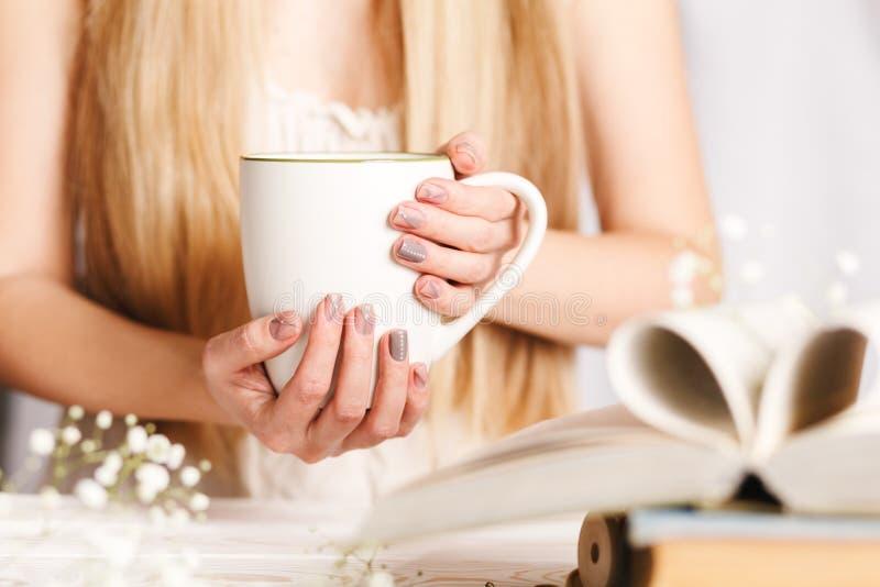 Een Kop thee in de handen van vrouwen Concept voor de lenteochtend Bloemthee in een witte Kop op de lijst met boeken en bloemen stock afbeelding