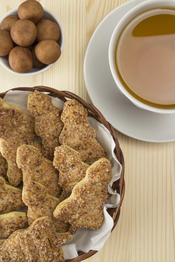 Een kop thee, marsepeinsuikergoed en koekjes in de vorm van een nieuw-jaarboom Theelijst, groene thee in witte havermoutpap, eige stock afbeelding