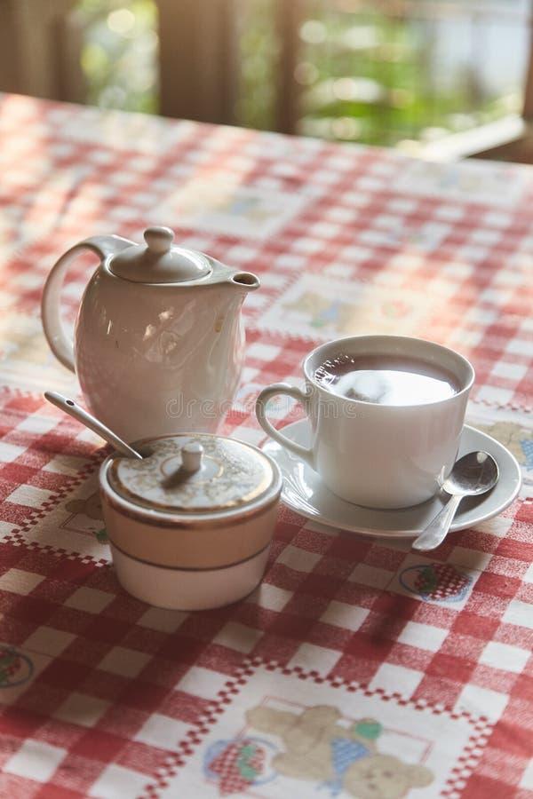Een kop thee met een theepot op de lijst Een Kop die van vers gebrouwen zwarte thee, aan stoom, warm zacht licht ontsnappen royalty-vrije stock afbeeldingen