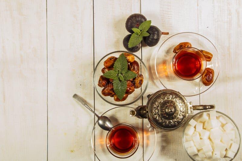 Een kop thee op een witte lijst Traditionele Arabische, Turkse Ramadanthee met droge data en rozijnen op een houten witte lijst t royalty-vrije stock fotografie