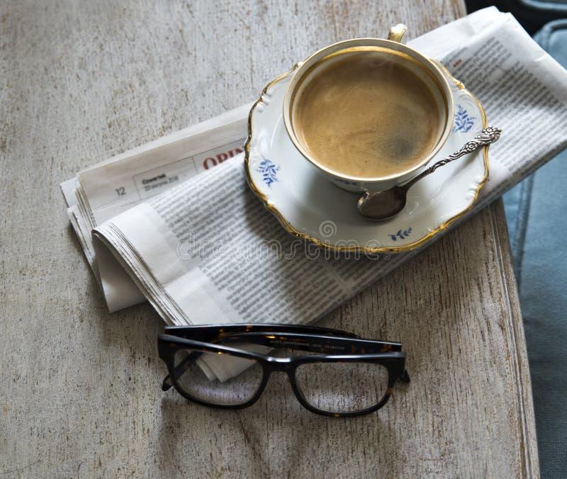 Een kop van aromatische sterke koffie op een schotel met een uitstekende lepel Krant en glazen op de lijst royalty-vrije stock afbeelding