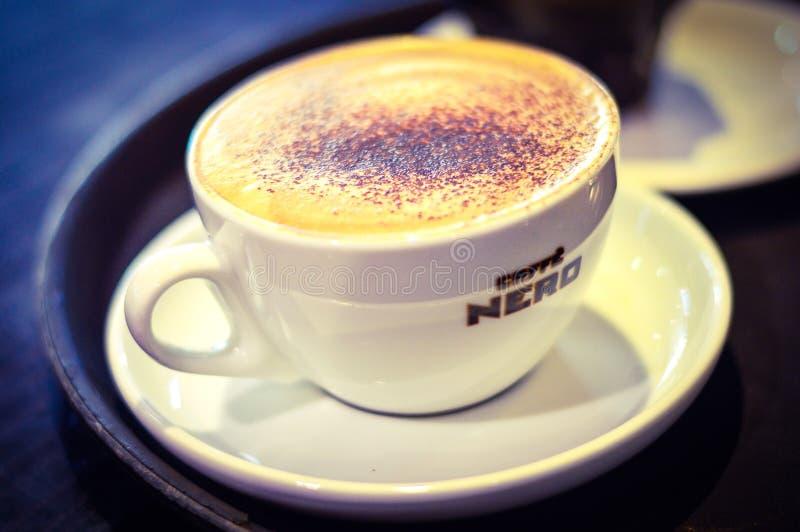 Een Kop van Cappuccino op Lijst in Caffe Nero, het UK wordt geplaatst dat royalty-vrije stock afbeeldingen
