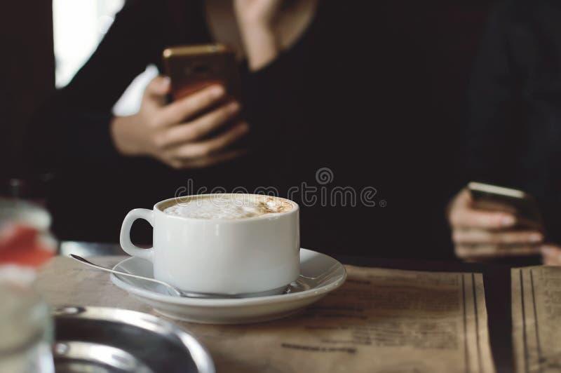 Een kop van cappuccinokoffie op een lijst in een koffie De mensen drinken koffie in een koffie en gebruiks mobiele telefoons Clos royalty-vrije stock fotografie
