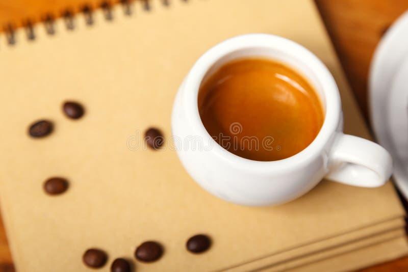 Een Kop van espresso met schuim en een notitieboekje, verspreide koffiebonen op een houten lijst Mens die een koffiepauze neemt stock afbeeldingen