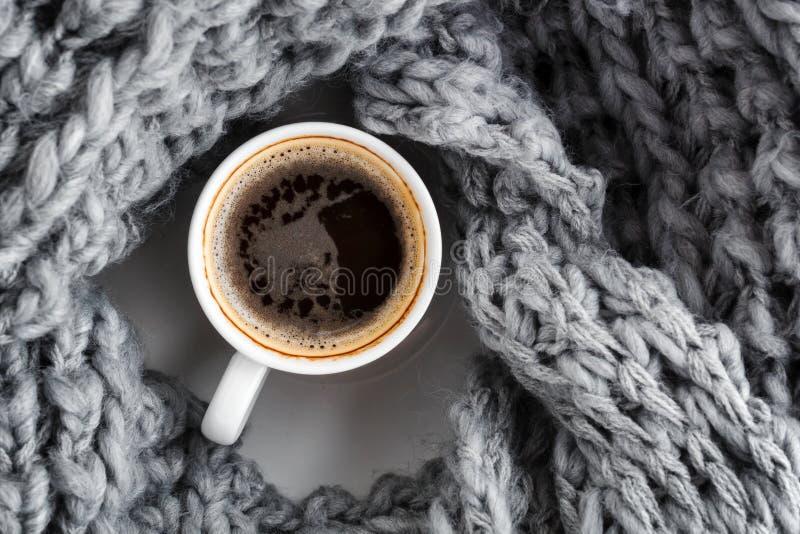 een kop van espresso, in een wollen warme grijze sjaal wordt verpakt die Hoogste mening stock foto