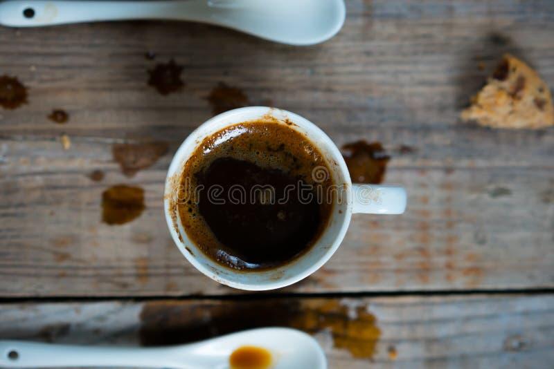 Een kop van gemorste koffie met een lepel en koekjescrumbs stock foto's