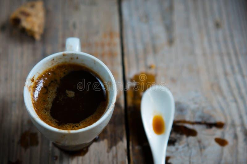Een kop van gemorste koffie met een lepel en koekjescrumbs stock foto