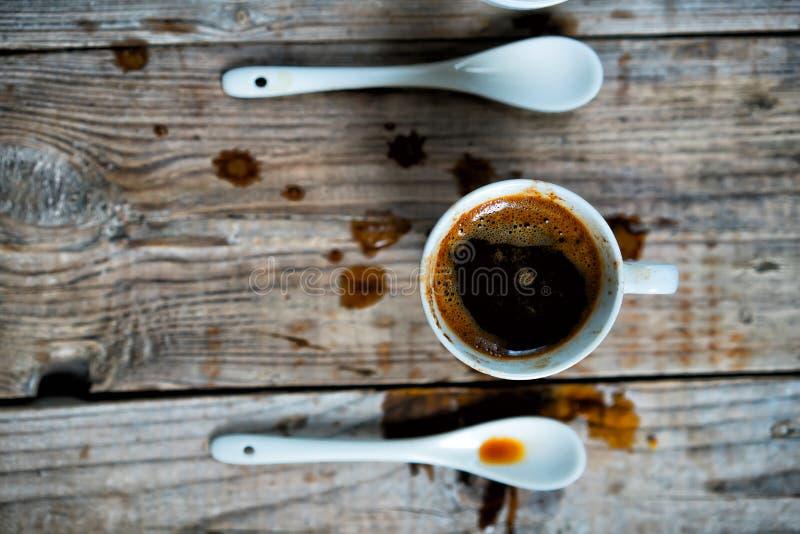 Een kop van gemorste koffie met een lepel op een houten achtergrond royalty-vrije stock afbeelding