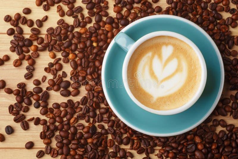 Een kop van geurige koffie in schuim op een houten lijst Latteart. De bonen van de koffie stock foto