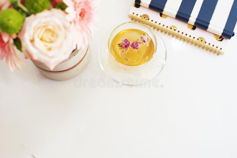 Een kop van gezond aftreksel met droge rozen Mooie verse bloemen, notitieboekjes op lichte marmeren lijst, hoogste mening Roze ro royalty-vrije stock foto's