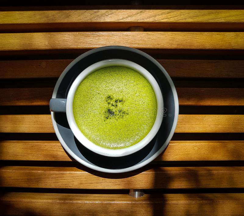 Een kop van groene matcha latte op houten lijst royalty-vrije stock fotografie