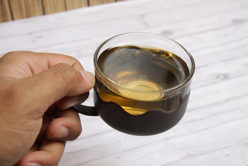Een kop van groene thee met chocospaanders cookiesMen de hand van ` s houdend een kop van groene te drinken thee royalty-vrije stock foto's