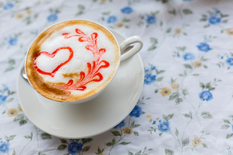 Een Kop van hete cappuccino met een patroon van een rood hart op de lijst met een tafelkleed in een bloem in een koffiewinkel Clo royalty-vrije stock afbeelding