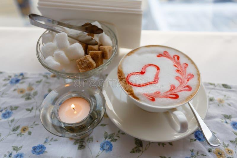 Een Kop van hete cappuccino met een patroon van een rood hart op de lijst met een tafelkleed in een bloem in een koffiewinkel Dic stock afbeelding