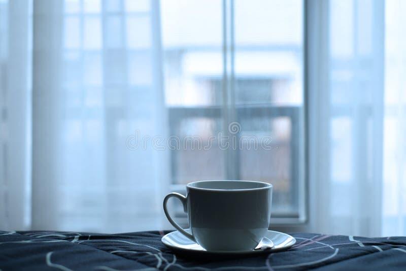 Een kop van hete koffie in bed met aardige mening en wit gordijn van venster royalty-vrije stock afbeelding