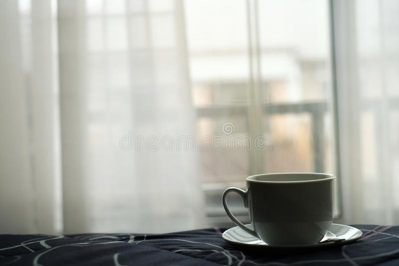 Een kop van hete koffie in bed met aardige mening en wit gordijn van venster royalty-vrije stock foto's
