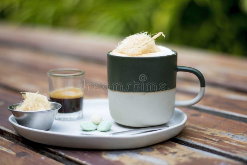 Een kop van Hete Koffie met extra geschotene, suikergesponnen suiker en met Thaise traditionele snacks op witte plaat stock fotografie