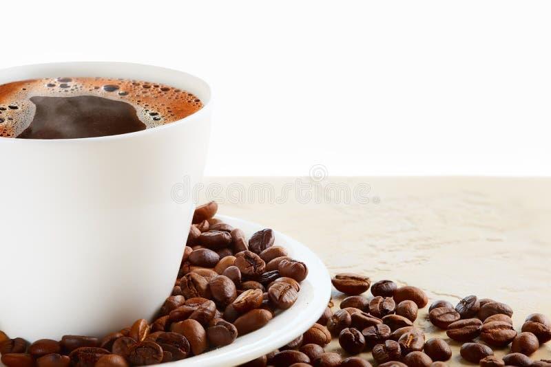 Een kop van hete koffie met koffiebonen op een witte achtergrond stock afbeeldingen