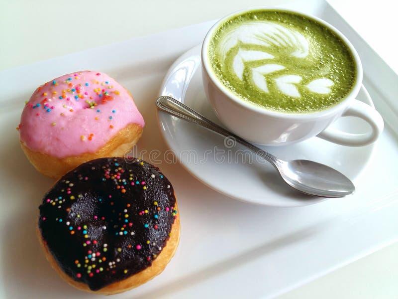 Een kop van hete matcha latte en doughnut zo heerlijk op wit royalty-vrije stock foto
