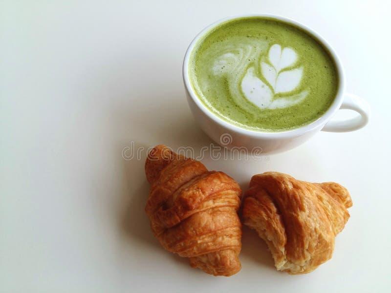 Een kop van hete matcha latte zo heerlijk met croissants op wit stock fotografie