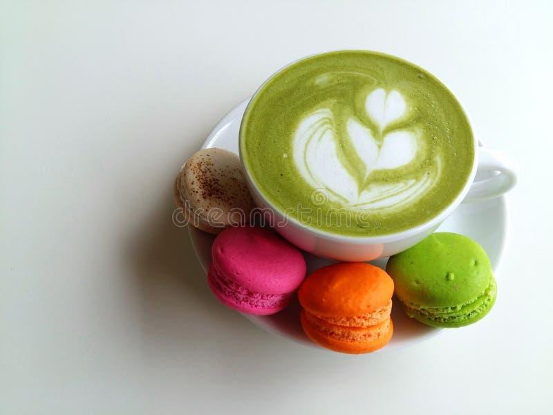Een kop van hete matcha latte zo heerlijk met makaron stock foto