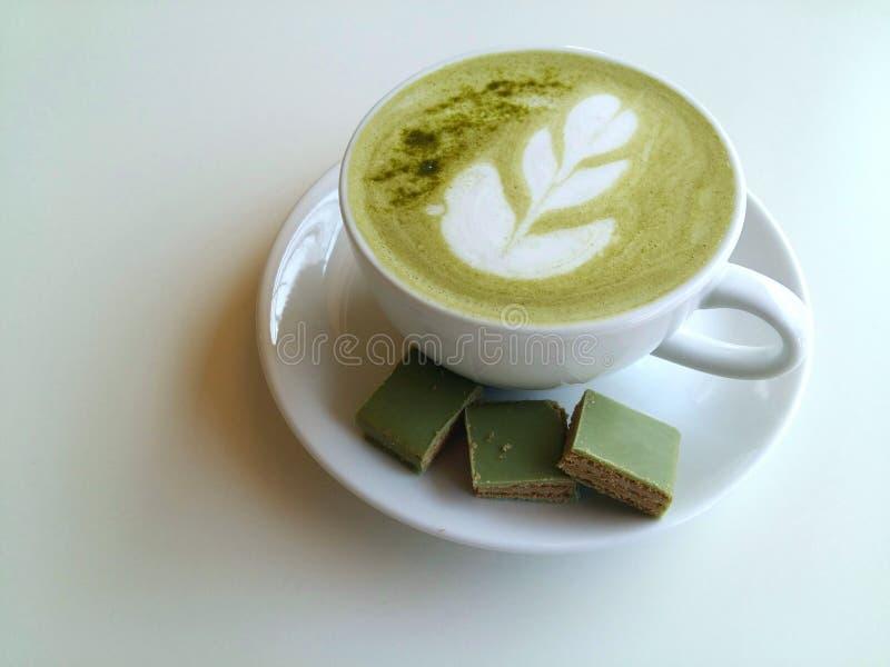 Een kop van hete matcha latte zo heerlijk met waffer op wit stock afbeeldingen