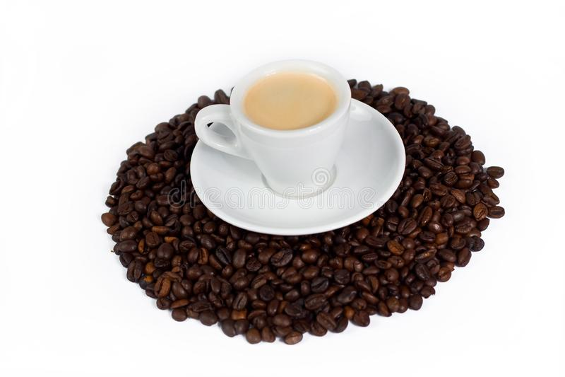 Een kop van koffie bovenop koffiebonen
