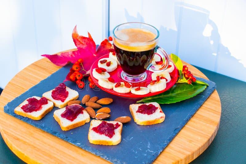 Een kop van koffie, brood met confiture, amandelen, banaan stock foto