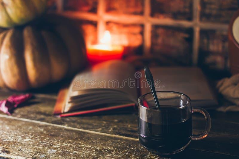 Een kop van koffie in comfortabele rustieke de herfstatmosfeer met de kaarsen en een boek stock fotografie