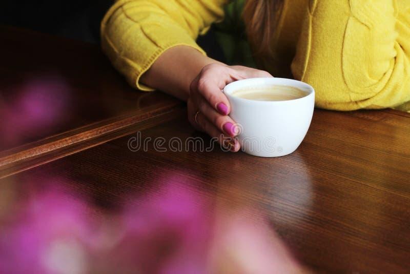 Een kop van koffie in de handen van een meisje stock foto