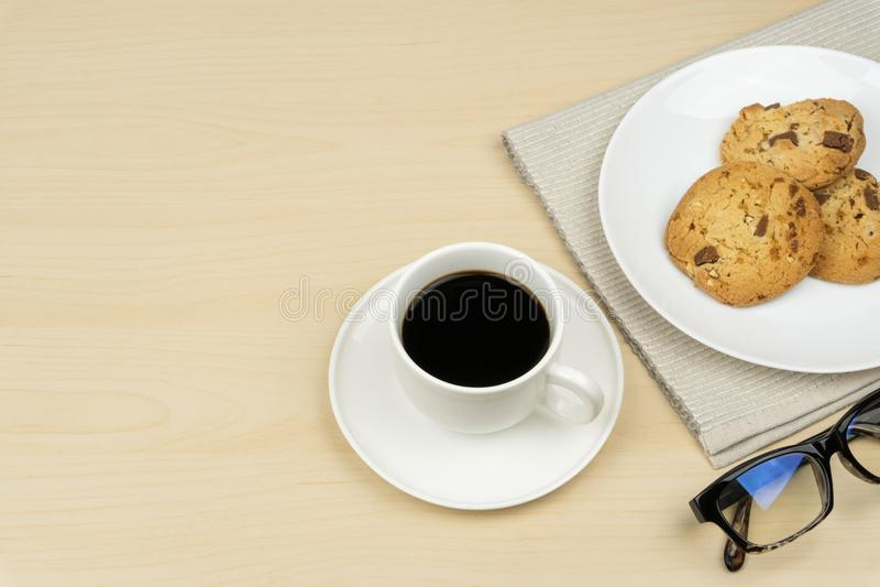 Een kop van koffie, drie stukken chocoladeschilferkoekjes in een witte ronde schotel royalty-vrije stock fotografie