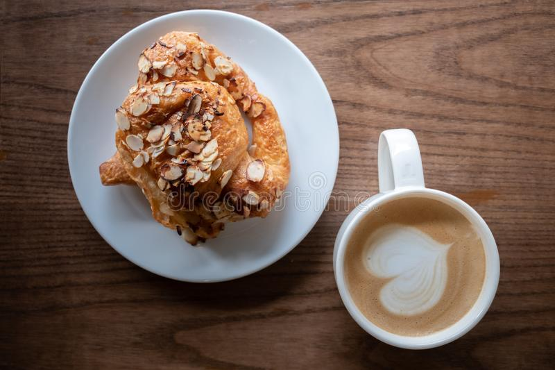 Een kop van koffie met amandelcroissant in de ochtend royalty-vrije stock afbeelding