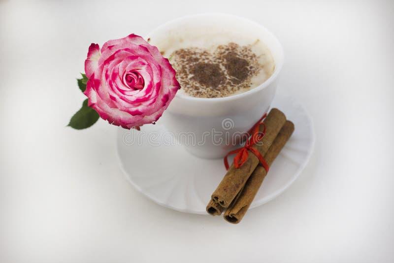 Een kop van koffie met kaneel op een witte achtergrond Roze rozenochtend royalty-vrije stock afbeeldingen
