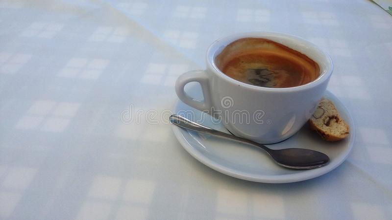 Een kop van koffie op een wit tafelkleed stock foto