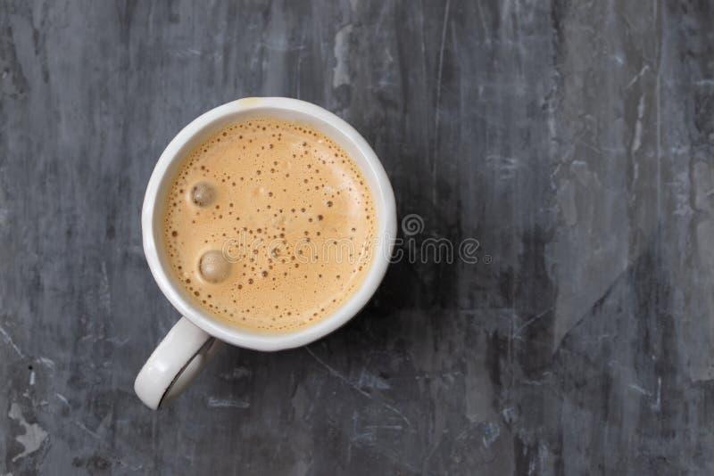 Een kop van koffie op grijze ceramische achtergrond stock afbeelding