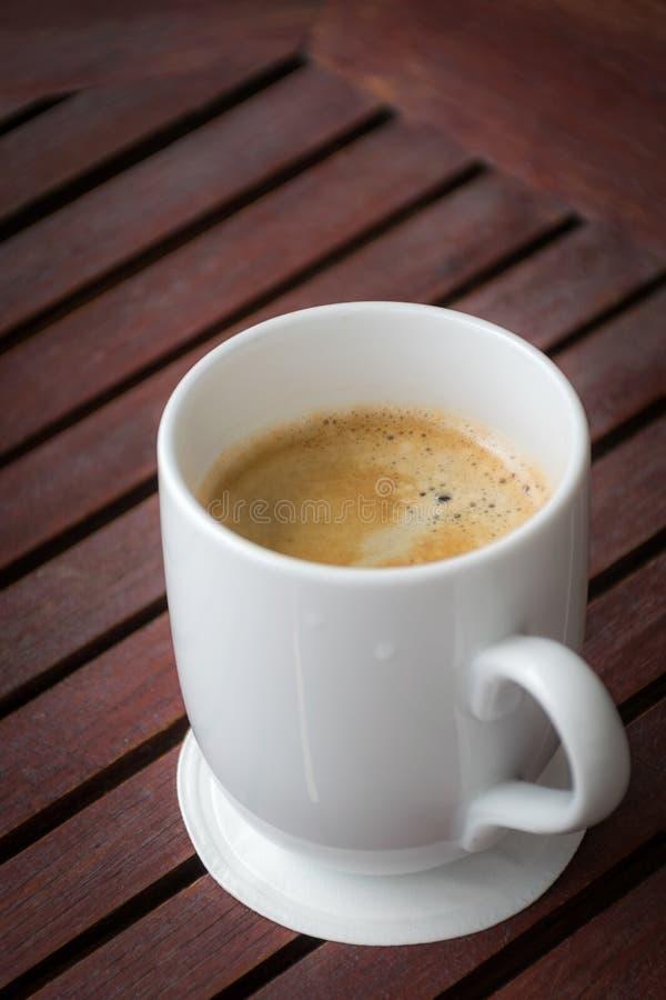 Een kop van koffie op een houten lijst royalty-vrije stock foto's