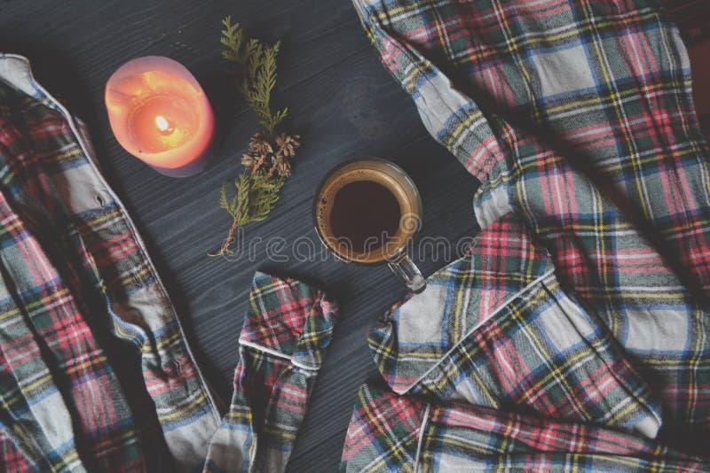 Een kop van koffie, pyjama's en aangestoken kaars op de houten achtergrond Comfortabele huisstijl Atmosferisch beeld stock afbeelding