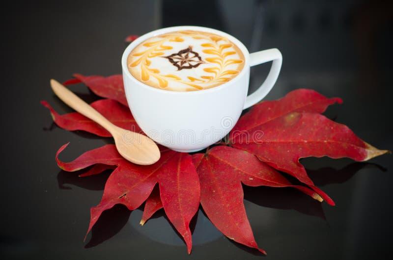 Een kop van lattekunst en esdoorn doorbladert royalty-vrije stock foto's