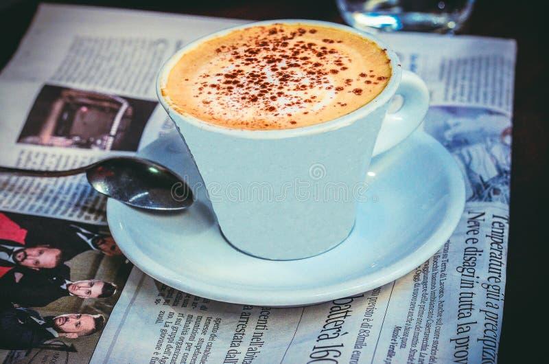 Een kop van vers gebrouwen cappuccino op de lijst met krant royalty-vrije stock foto
