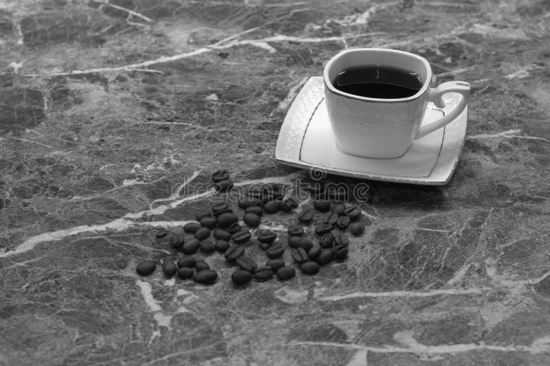 Een kop van zwarte koffie en de korrels liggen op een marmeren lijst zwart wit schot royalty-vrije stock afbeeldingen